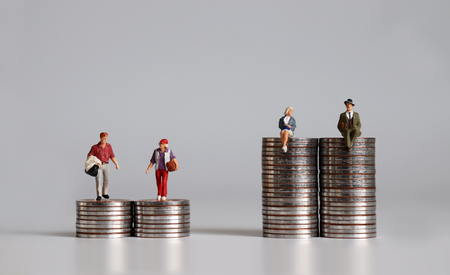 Miniature people with pile of coins. The concept of social stratification according to income differences.
