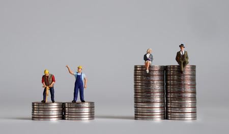 Personnes miniatures avec tas de pièces de monnaie. Un concept de disparité de revenu. Banque d'images