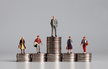 Miniature people with stack of coins. A concept of income inequality. 版權商用圖片