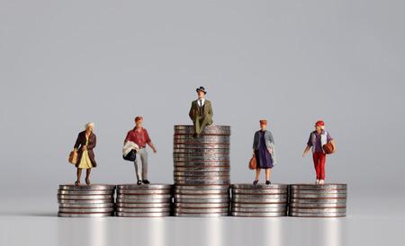 Notion de stratification sociale. Personnes miniatures avec pile de pièces.