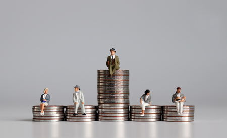 Miniature people with stack of coins. The concept is rich and poor.
