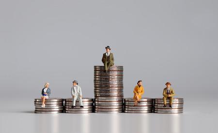 Persone in miniatura con pila di monete. Una nozione di disuguaglianza economica.