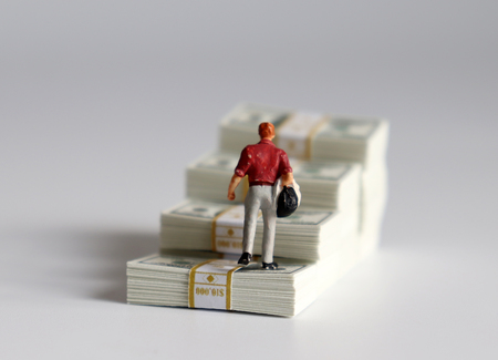 The back of a miniature man walking over a stack of cascaded bills. 写真素材
