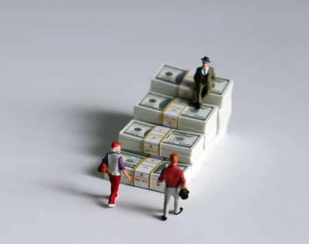 Miniature people and a pile of banknotes stacked in the shape of a staircase.
