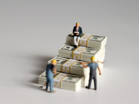 Miniature people. The pile of banknotes is stacked in the shape of a staircase. 版權商用圖片