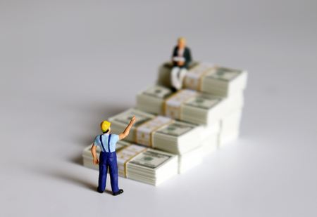 Miniature people. The banknotes in the shape of a staircase. Stock Photo