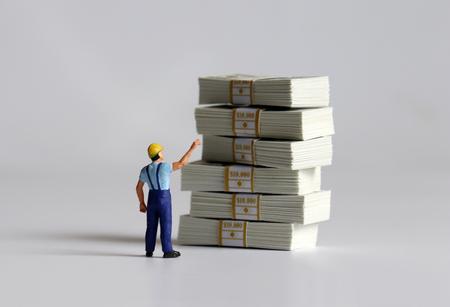 Le dos d'un homme miniature pointant vers une liasse de billets et ça.