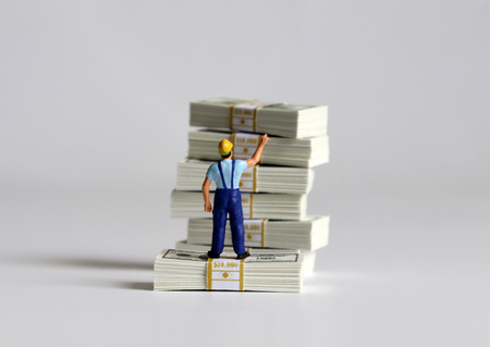 The back of a miniature man pointing at a bundle of bills and it.