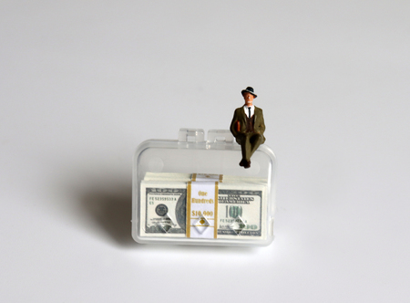 A miniature businessman sitting on a bag with a hundred-dollar bills.
