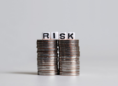 RISK text white cube on two pile of coins.
