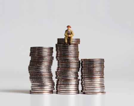 Ein Miniaturmann, der auf einem Haufen Münzen sitzt. Standard-Bild