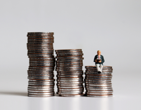 A miniature man sitting on a pile of coins reading a book.
