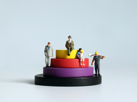 Round wooden blocks and miniature people. The concept of social stratification.