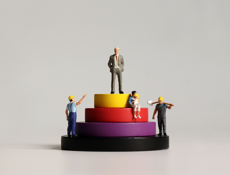 Concept of social stratification. Round wooden blocks and miniature people. Stock Photo
