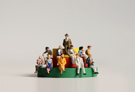 Miniature people sitting on wooden blocks.