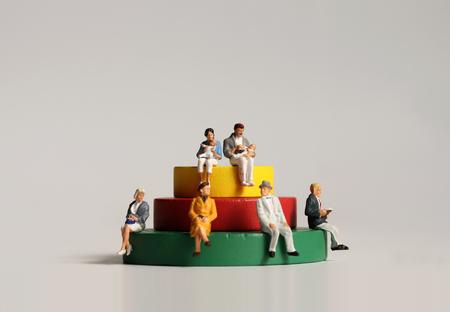 Miniaturmenschen sitzen auf Holzklötzen.