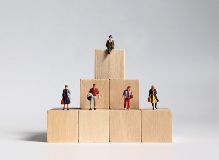 Wooden blocks and miniature people. Concept of layered social structure.