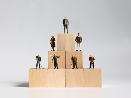 Wooden blocks and miniature people. The concept of social stratification.