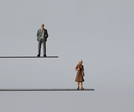 A miniature man and a miniature woman standing at different heights. The concept of discrimination in employment by gender.