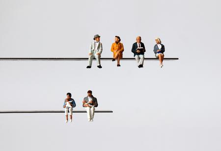 El concepto de una sociedad que envejece y una tasa de natalidad baja. Gente en miniatura. Foto de archivo
