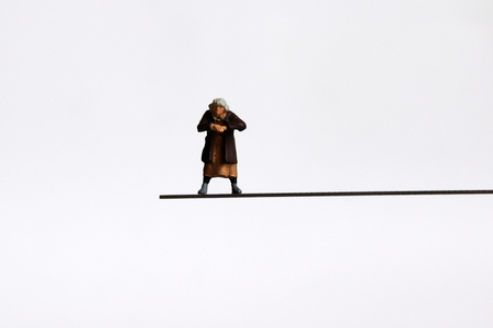 A miniature woman standing on a cliff. Imagens