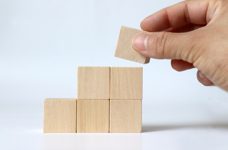 A hand piling up a wooden block with a staircase shape.