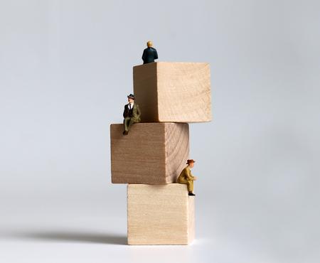 Miniature people sitting between piles of wooden blocks.