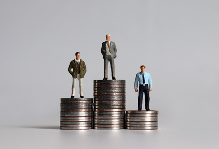 Miniature people standing on piles of coins of three different heights.
