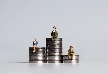 Des personnages miniatures assis sur des tas de pièces de trois hauteurs différentes.