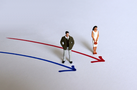 Miniature people standing next to arrows of different colors.