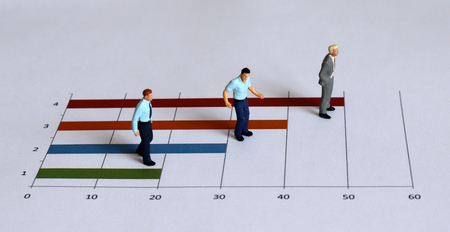 Miniature people standing on the bar graph. Stock Photo