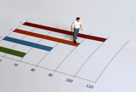 A miniature old man walking on a bar graph. Stock fotó