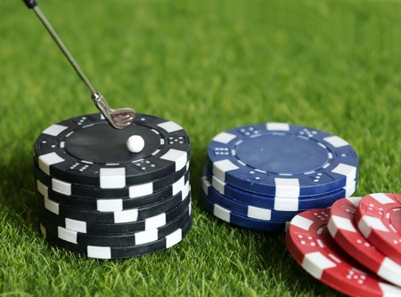 Casino chips and golf equipment on the green lawn.