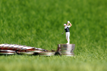 A miniature golfer standing over a pile of coins on the green lawn background.