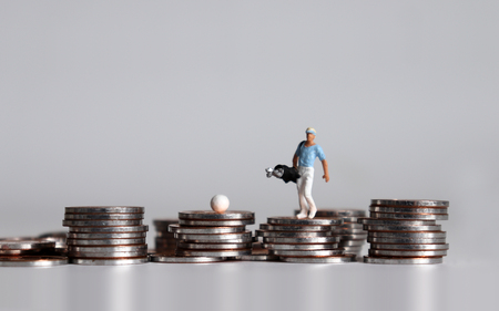 A miniature man walking on a pile of coins with a golf bag.