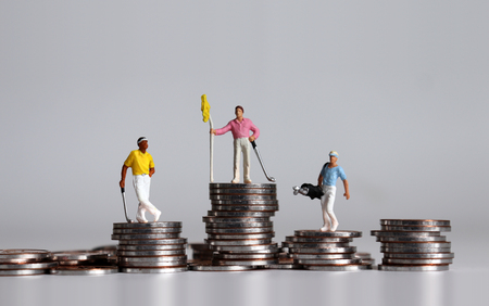Miniature golfers standing on piles of different heights. Foto de archivo