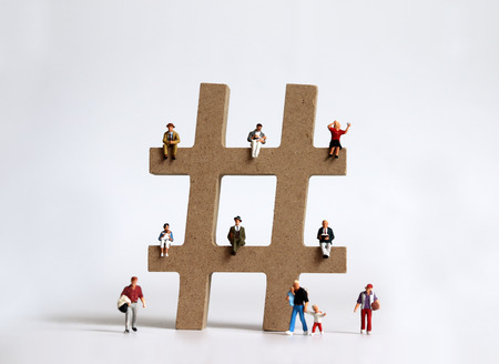 Hash tag sign wooden block with various miniature people.