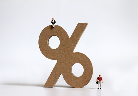 Wooden block of% mark and miniature people.