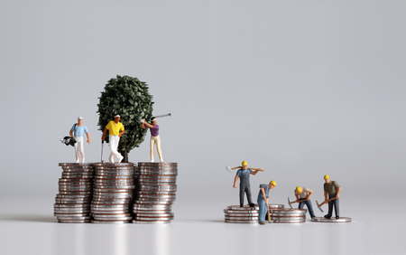 Miniature people and pile of coins. Concepts about the lives of the rich and the poor.