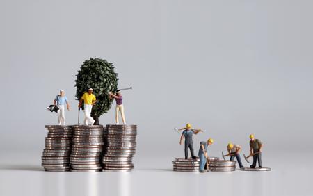 Personnes miniatures et tas de pièces de monnaie. Concepts sur la vie des riches et des pauvres.