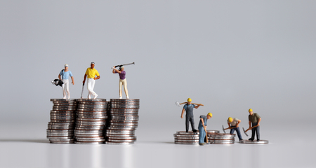 Miniature people standing on a pile of coins. A concept of income disparity. Archivio Fotografico