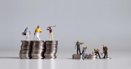 Miniatuurmensen die zich op een stapel muntstukken bevinden. Een concept van inkomensongelijkheid.