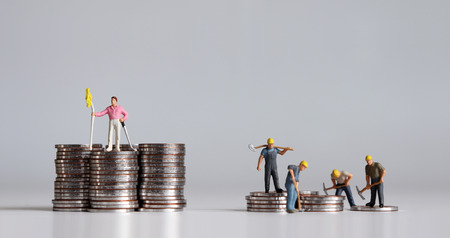 Coins and miniature people. Concept of income inequality.