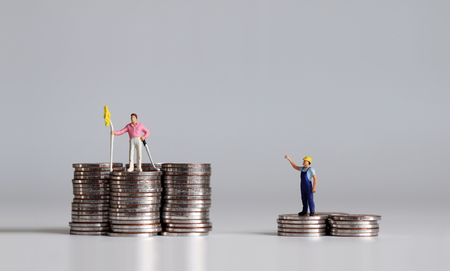 Concept of economic inequality. Coins and miniature people.