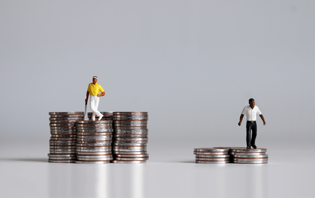Coins and miniature people. 版權商用圖片