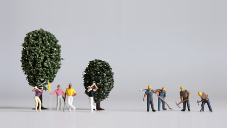 Miniature people and miniature trees. Concept of the gap between rich and poor.