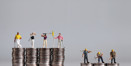 Miniature people standing on a pile of coins. Concept of the gap between rich and poor.