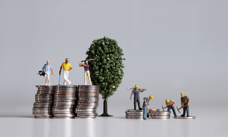 Miniature people standing on a pile of coins. Concepts about the lives of the rich and the poor.