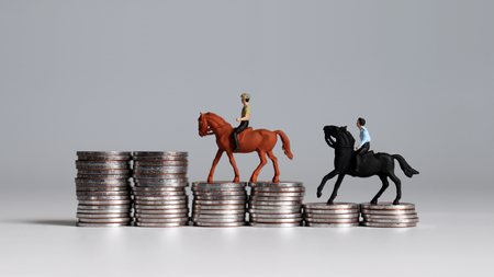 Miniature men riding horse on coin stacks. Stock Photo