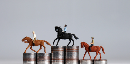 Three miniature men riding horses on piles of coins. Three piles of coins in the shape of a podium.